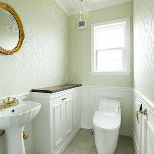 東京都下のヴィクトリアン調のおしゃれなトイレ・洗面所 (落し込みパネル扉のキャビネット、白いキャビネット、緑の壁、コンソール型シンク、グレーの床) の写真