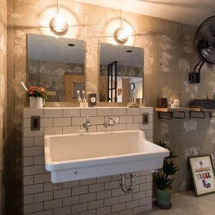 札幌のインダストリアルスタイルのおしゃれなトイレ・洗面所 (グレーの壁、コンクリートの床、壁付け型シンク、グレーの床) の写真