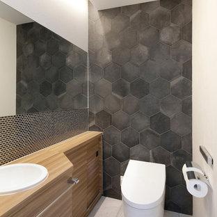 Свежая идея для дизайна: туалет среднего размера в стиле модернизм с фасадами островного типа, светлыми деревянными фасадами, унитазом-моноблоком, черной плиткой, керамогранитной плиткой, белыми стенами, полом из керамогранита, накладной раковиной, столешницей из ламината, серым полом и бежевой столешницей - отличное фото интерьера