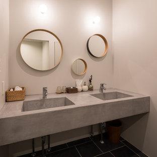 他の地域, のコンテンポラリースタイルのおしゃれなトイレ・洗面所 (グレーの壁、一体型シンク、黒い床) の写真
