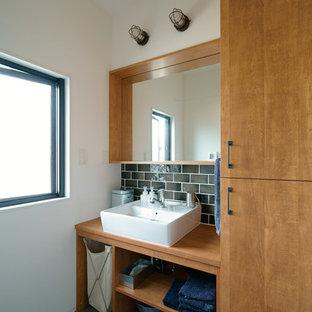 Свежая идея для дизайна: туалет в скандинавском стиле с плоскими фасадами, коричневыми фасадами, белыми стенами, настольной раковиной, столешницей из дерева, черным полом и коричневой столешницей - отличное фото интерьера