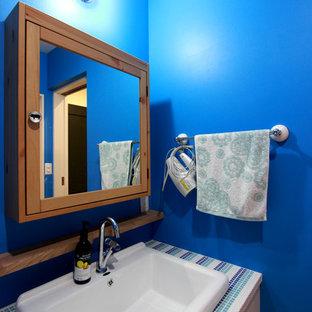 東京23区の広いカントリー風おしゃれなトイレ・洗面所 (フラットパネル扉のキャビネット、中間色木目調キャビネット、青い壁、オーバーカウンターシンク、タイルの洗面台、青い洗面カウンター) の写真