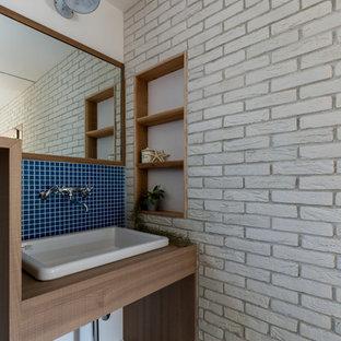 京都の中くらいのアジアンスタイルのおしゃれなトイレ・洗面所 (オープンシェルフ、中間色木目調キャビネット、分離型トイレ、白いタイル、磁器タイル、白い壁、コンクリートの床、ベッセル式洗面器、ラミネートカウンター、グレーの床、ベージュのカウンター) の写真