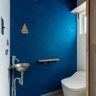Идея дизайна: туалет среднего размера в восточном стиле с открытыми фасадами, фасадами цвета дерева среднего тона, раздельным унитазом, белой плиткой, керамогранитной плиткой, белыми стенами, бетонным полом, настольной раковиной, столешницей из ламината, серым полом и бежевой столешницей