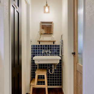 Immagine di un piccolo bagno di servizio nordico con nessun'anta, ante bianche, WC sospeso, piastrelle blu, piastrelle di vetro, pareti bianche, pavimento in compensato, lavabo sospeso, top in quarzo composito, pavimento marrone, top marrone, mobile bagno sospeso, soffitto in carta da parati e carta da parati