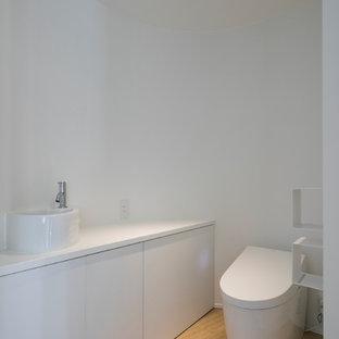 横浜のモダンスタイルのおしゃれなトイレ・洗面所 (フラットパネル扉のキャビネット、白いキャビネット、白い壁、無垢フローリング、ベッセル式洗面器、茶色い床) の写真