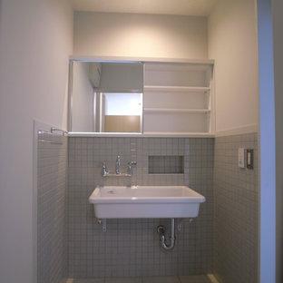 Foto de aseo de estilo zen con baldosas y/o azulejos grises, baldosas y/o azulejos de cerámica, paredes grises, suelo de baldosas de cerámica, lavabo suspendido y suelo beige
