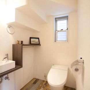 Пример оригинального дизайна: туалет в современном стиле с плоскими фасадами, белыми фасадами, белыми стенами, деревянным полом, настольной раковиной, столешницей из дерева, коричневым полом и коричневой столешницей