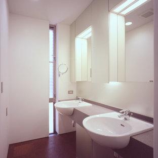 Cette image montre un grand WC et toilettes minimaliste avec un placard à porte vitrée, des portes de placard blanches, un mur blanc, un sol en liège, un lavabo posé, un plan de toilette en surface solide et un sol marron.