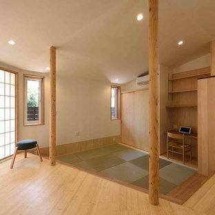 Inspiration pour une salle de séjour avec une bibliothèque ou un coin lecture chalet de taille moyenne et ouverte avec un mur blanc, un sol de tatami, un téléviseur fixé au mur et un sol vert.