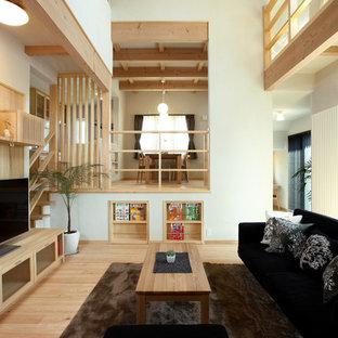 他の地域のアジアンスタイルのおしゃれなオープンリビング (白い壁、淡色無垢フローリング、据え置き型テレビ、ベージュの床) の写真