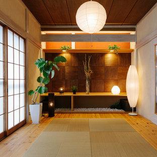 Réalisation d'une petit salle de séjour asiatique avec un mur rouge, aucune cheminée, aucun téléviseur, un sol de tatami et un sol beige.