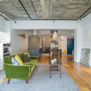 東京23区のインダストリアルスタイルのおしゃれなファミリールーム (白い壁、無垢フローリング、据え置き型テレビ、茶色い床) の写真