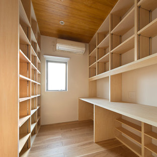Imagen de sala de estar con biblioteca cerrada, moderna, pequeña, sin televisor, con paredes blancas, suelo de contrachapado y suelo beige