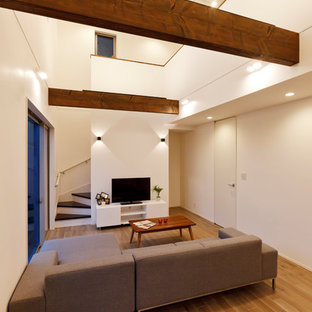 他の地域のコンテンポラリースタイルのおしゃれなファミリールーム (白い壁、淡色無垢フローリング、据え置き型テレビ、ベージュの床、暖炉なし) の写真