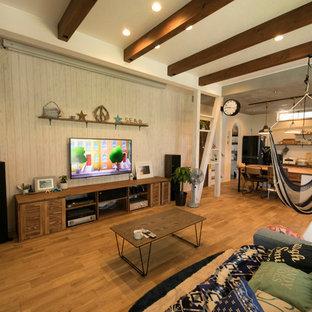 他の地域のビーチスタイルのおしゃれなファミリールーム (白い壁、無垢フローリング、壁掛け型テレビ、茶色い床) の写真
