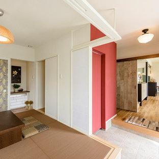 Cette image montre une salle de séjour design avec un mur blanc, un sol de tatami et un sol marron.