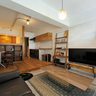 他の地域のインダストリアルスタイルのおしゃれなファミリールーム (白い壁、コンクリートの床、暖炉なし、据え置き型テレビ) の写真