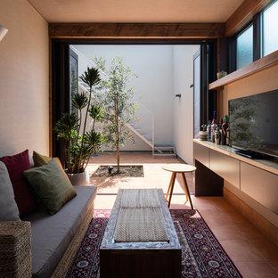 Idee per un soggiorno etnico chiuso con pareti bianche, pavimento in terracotta, TV autoportante, pavimento arancione e angolo bar