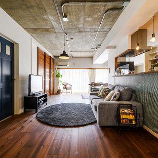 他の地域のインダストリアルスタイルのおしゃれなファミリールーム (白い壁、濃色無垢フローリング、据え置き型テレビ、茶色い床) の写真