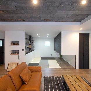 他の地域のインダストリアルスタイルのおしゃれなオープンリビング (白い壁、無垢フローリング、壁掛け型テレビ、茶色い床) の写真