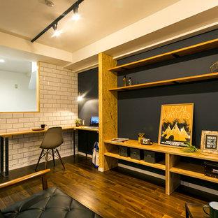 他の地域のインダストリアルスタイルのおしゃれなファミリールーム (黒い壁、濃色無垢フローリング、茶色い床) の写真