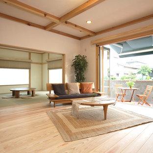 他の地域のアジアンスタイルのおしゃれなファミリールーム (白い壁、淡色無垢フローリング、ベージュの床) の写真