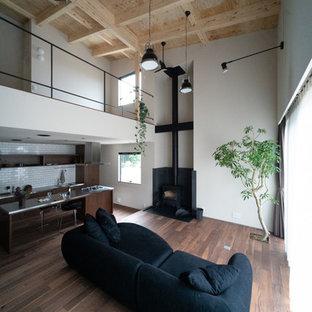 Imagen de sala de estar abierta, de estilo zen, con paredes beige, suelo de madera oscura, estufa de leña, marco de chimenea de hormigón y televisor independiente