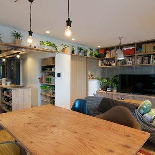 Imagen de sala de estar abierta, urbana, sin chimenea, con paredes blancas, suelo de madera clara y televisor independiente