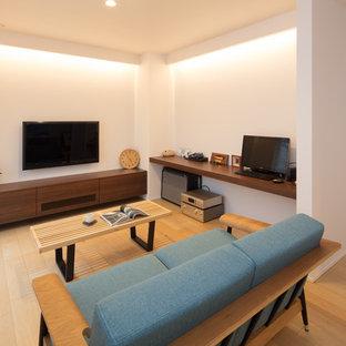他の地域のモダンスタイルのおしゃれなファミリールーム (白い壁、淡色無垢フローリング、壁掛け型テレビ、ベージュの床) の写真