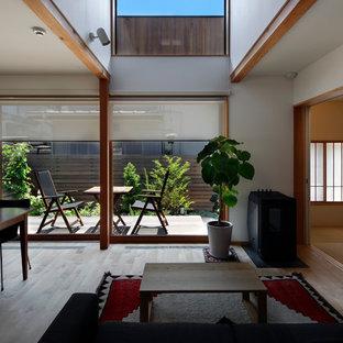 東京都下のコンテンポラリースタイルのおしゃれなファミリールーム (白い壁、淡色無垢フローリング、壁掛け型テレビ、ベージュの床) の写真