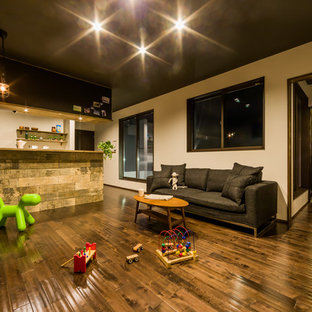 他の地域のインダストリアルスタイルのおしゃれなファミリールーム (白い壁、無垢フローリング、茶色い床) の写真
