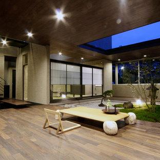 他の地域のアジアンスタイルのおしゃれなファミリールーム (ベージュの壁、無垢フローリング、茶色い床) の写真