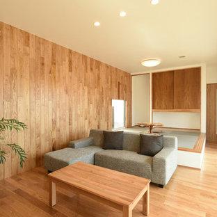他の地域のモダンスタイルのおしゃれなファミリールーム (マルチカラーの壁、淡色無垢フローリング、茶色い床) の写真