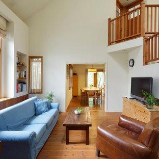 他の地域の大きいカントリー風おしゃれなファミリールーム (白い壁、無垢フローリング、暖炉なし、据え置き型テレビ、茶色い床) の写真