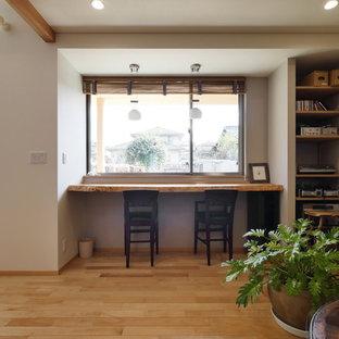 他の地域のアジアンスタイルのおしゃれなファミリールーム (ミュージックルーム、白い壁、無垢フローリング、茶色い床) の写真