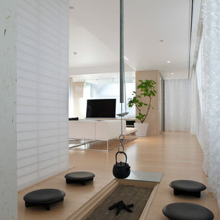 Foto på ett orientaliskt allrum med öppen planlösning, med vita väggar, ljust trägolv och en fristående TV