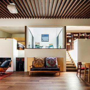 他の地域のコンテンポラリースタイルのおしゃれなファミリールーム (薪ストーブ、据え置き型テレビ、白い壁、無垢フローリング、茶色い床) の写真