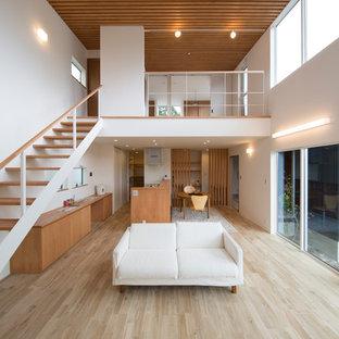 他の地域, のアジアンスタイルのおしゃれなファミリールーム (白い壁、塗装フローリング、茶色い床) の写真