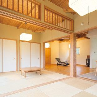 他の地域の和風のおしゃれなファミリールーム (白い壁、無垢フローリング、薪ストーブ、レンガの暖炉まわり、茶色い床) の写真