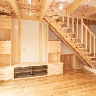 Foto de sala de estar con barra de bar abierta, asiática, de tamaño medio, con paredes blancas, suelo de madera en tonos medios, televisor colgado en la pared y suelo marrón
