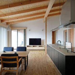 Nordisches Wohnzimmer mit weißer Wandfarbe, hellem Holzboden, Eckkamin, freistehendem TV, freigelegten Dachbalken und Tapetenwänden in Sonstige