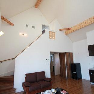 他の地域のコンテンポラリースタイルのおしゃれなファミリールーム (白い壁、淡色無垢フローリング、薪ストーブ、レンガの暖炉まわり、壁掛け型テレビ) の写真