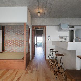東京23区の中サイズのおしゃれなファミリールーム (ホームバー、グレーの壁、無垢フローリング、暖炉なし、壁掛け型テレビ、茶色い床) の写真
