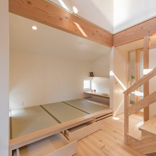 Exemple d'une salle de séjour asiatique fermée avec un mur blanc, un sol en bois clair et un sol beige.