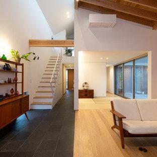 他の地域のモダンスタイルのおしゃれなオープンリビング (白い壁、無垢フローリング、コーナー設置型暖炉、石材の暖炉まわり、壁掛け型テレビ、黒い床) の写真
