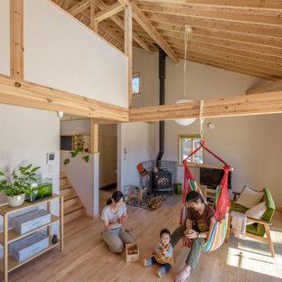 Diseño de sala de estar abierta con paredes blancas, suelo de madera clara, estufa de leña, marco de chimenea de baldosas y/o azulejos, televisor independiente y suelo violeta