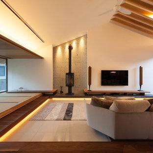 他の地域のコンテンポラリースタイルのおしゃれなファミリールーム (白い壁、壁掛け型テレビ、ベージュの床) の写真