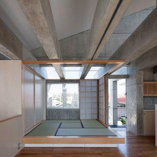 他の地域のアジアンスタイルのおしゃれなファミリールーム (グレーの壁、無垢フローリング、茶色い床) の写真