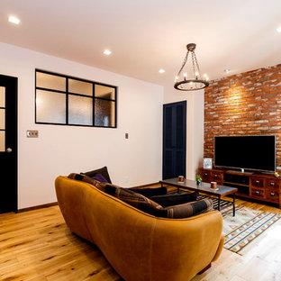 他の地域のインダストリアルスタイルのおしゃれなファミリールーム (白い壁、無垢フローリング、据え置き型テレビ、茶色い床) の写真